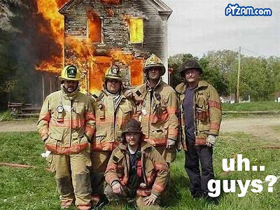 Bombeiros posam para fotografia em frente a uma construção em chamas.