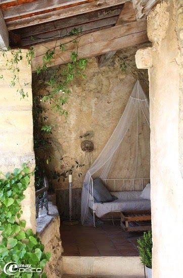 La terrasse couverte, son lit en fer forgé coiffé d'une moustiquaire