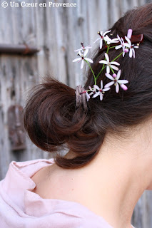 Few mauve flowers in hair