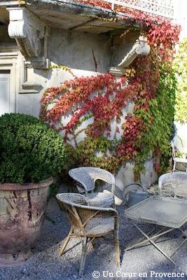 Mobilier de jardin en osier sous un balcon ouvragé