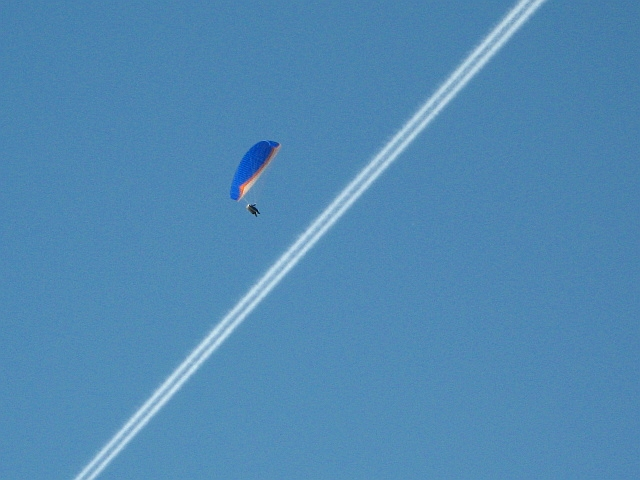 Paraglider passing through a smoke trail left by a plane