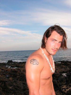 Masculine male on the beach showing his small oval shoulder tribal tattoo.