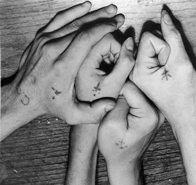 Tiny cross tattoos on hands.