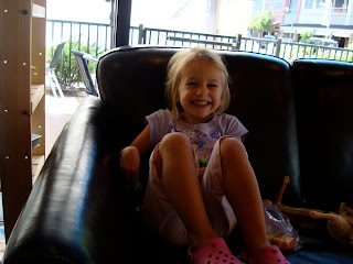 Young girl crouched up on couch smiling