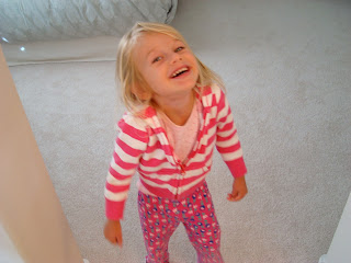 Young girl in doorway wearing pink and smiling