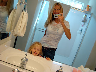 Woman and child taking picture together in mirror