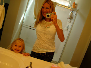 Woman and young girl smiling in bathroom mirror