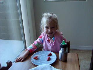 Young girl sitting at Childs table eating a plate of strawberries