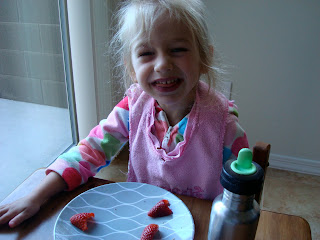 Young girl making silly face while eating strawberries