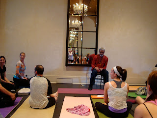 Dharma Mittra sitting addressing room full of people