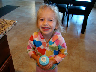 Young girl holding sippy cup smiling