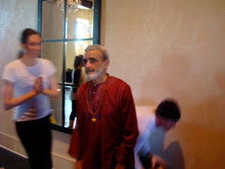 Dharma Mittra standing with two people in front of wall