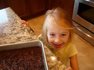 Little girl next to fudge on countertop with tongue out