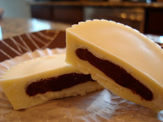 Vegan White Chocolate Chocolate-Peanut Butter Cup split in half on paper liner
