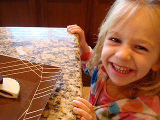 Young girl smiling in front of plate of peanut butter cups