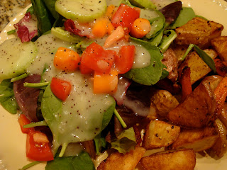 Mixed greens and vegetable salad with dressing served with roasted vegetables
