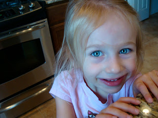 Young girl in kitchen holding onto countertop