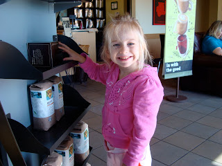 Young girl in pink standing looking at coffee products