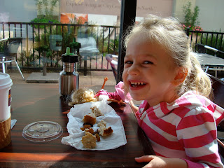 Young girl sitting at table eating snacks and smiling