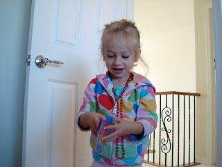 Young girl playing with book wearing beads