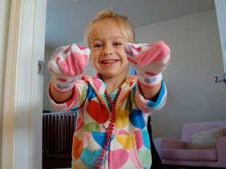 Young girl wearing socks on hands
