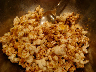 Popcorn in bowl being mixed up with spoon
