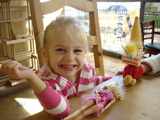 Young girl smiling at table playing with toys