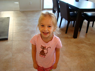Young girl in pink shirt standing in kitchen