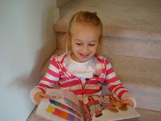 Young girl sitting on steps looking at catalog