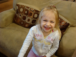 Smiling young girl on oversized chair