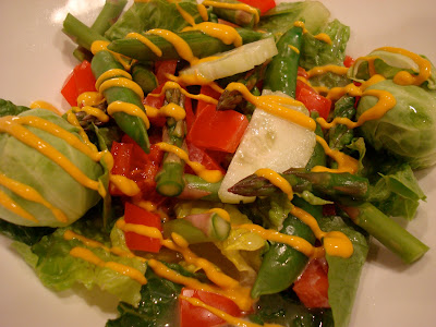 Green salad with mixed vegetables drizzled with mustard