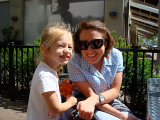 Lady in blue dress and young girl smiling outside at coffee shop