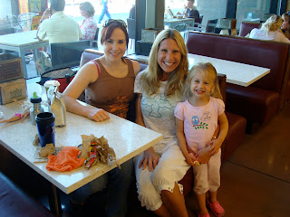 Two women in booth with child standing next to them