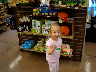 Young girl standing in front of toys in store