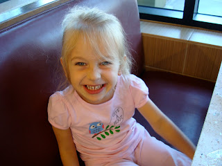 Young girl sitting in booth smiling