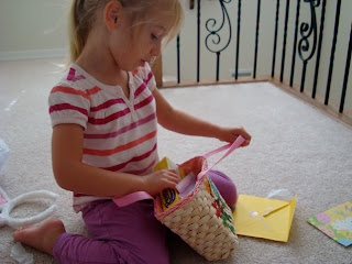Young girl looking in smaller easter basket