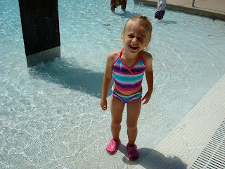 Young girl in swimsuit and crocs wading in pool