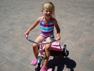 Young girl in swim suit riding tricycle