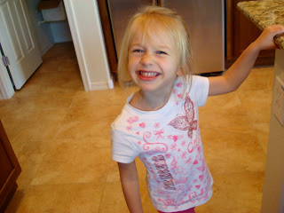 Young girl standing in kitchen smiling