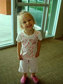 Young girl sanding next to door smiling