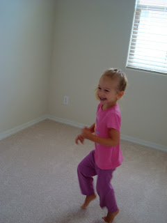 Little girl in pink and purple dancing in room