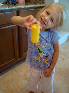 Young girl holding a piece of corn