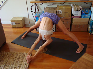 Woman doing prasaritta padonttanasana C yoga pose