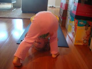 Little girl doing adho mukha savasan yoga pose