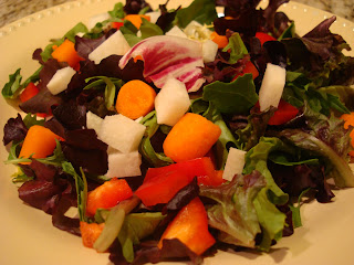Raw vegetables tossed together in round white shallow bowl