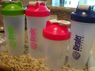 Various colors and sizes of blender bottles on countertop