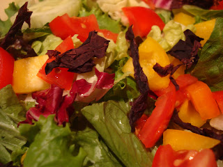 Close up of Dulse Flakes over a vegetable and greens salad