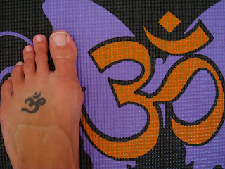 Foot with Om tattoo matching Om design on yoga mat