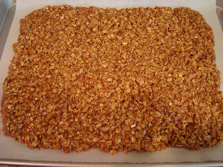 Granola spread out on parchment paper lined baking sheet