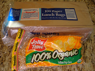 Paper lunch bags and organic yellow pop corn in packages on countertop